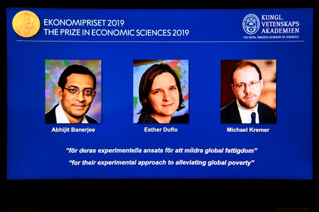 A computer screen displays the co-winners of the 2019 Sveriges Riksbank Prize in Economic Sciences in...