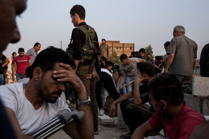 Syrians bury Syrian Democratic Forces fighters killed fighting Turkish advance in the Syrian town of Qamishli, Saturday, Oct.