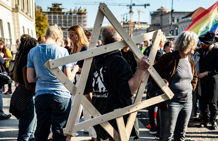 A demonstrator with a large wooden star of David over his shoulder participates in a protest against anti-Semitism.
