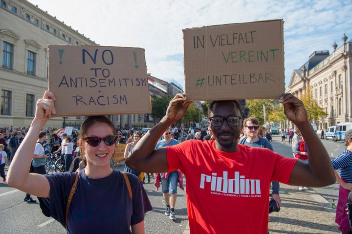"Hannah (26) and Kemo (30) hold posters with the inscription ""No to Antisemitism and Racism"" and ""United in Diversity - #Indiv"