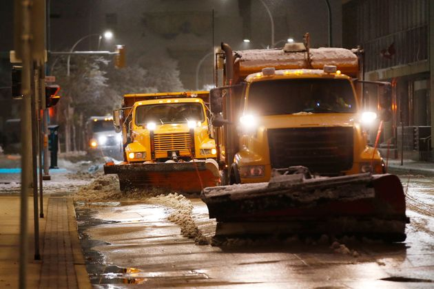 Crews clean up during an early storm, which caused caused fallen trees, many on cars, and power lines...