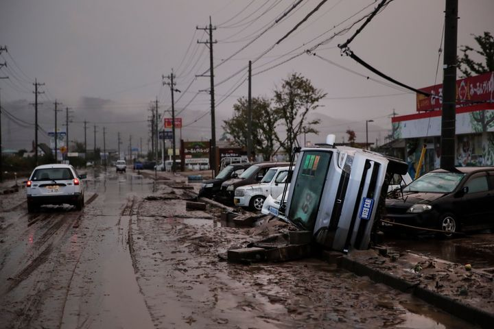 Typhoon-damaged cars sit on the street covered with mud on Monday in Hoyasu, Japan. Rescue crews in Japan dug through mudslid