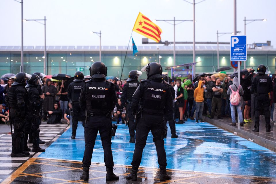 BARCELONA, SPAIN - OCTOBER 14: Police watch as protestors block the Barcelona Airport access in a protest...