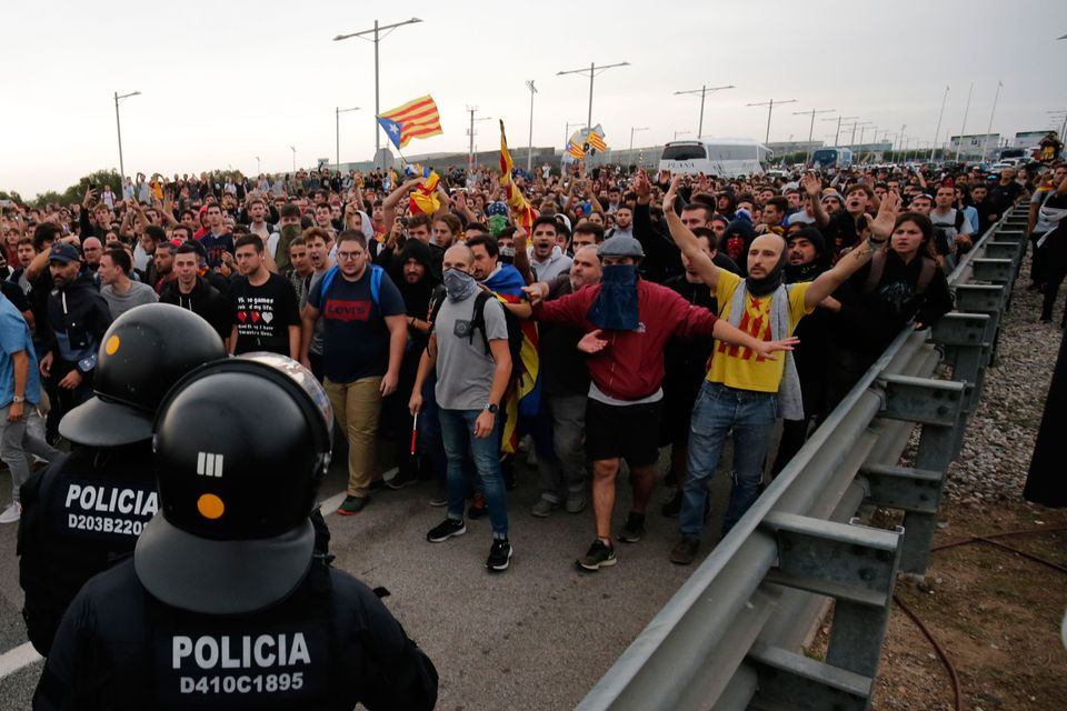 Protesters clash with Spanish policemen on the highway leading to El Prat airport in Barcelona on October...