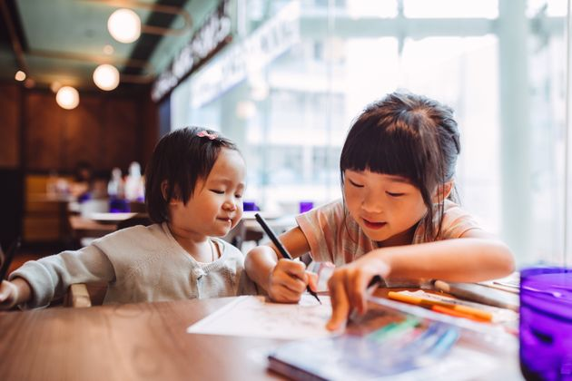 Little girl teaching her little toddler sister to draw joyfully in a