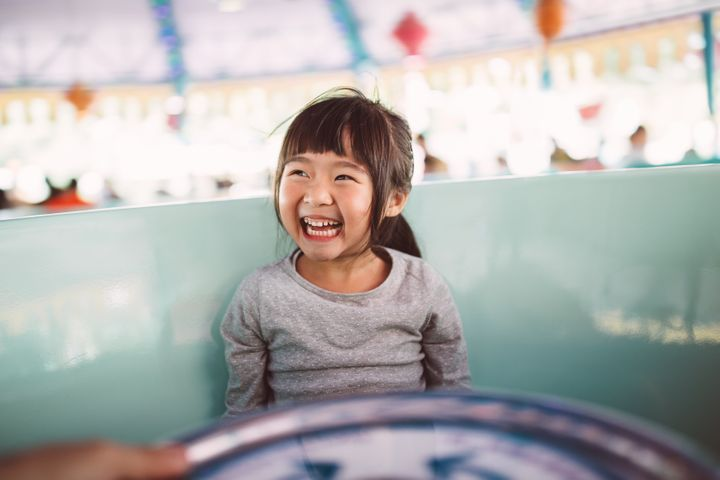 Lovely little girl riding on the amusement park ride joyfully.