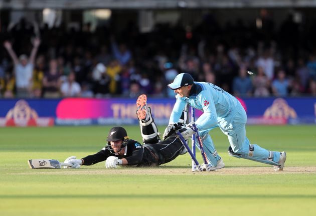 England's Jos Buttler runs out New Zealand's Martin Guptill during the Super Over in the Cricket World...