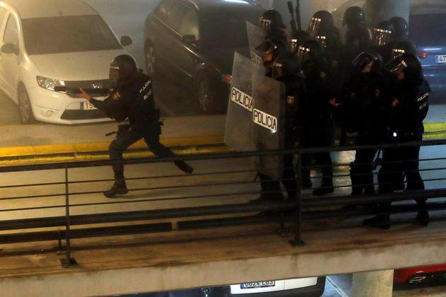 Policías antidisturbios durante los altercados que se han producido en el parking del aeropuerto El Prat...