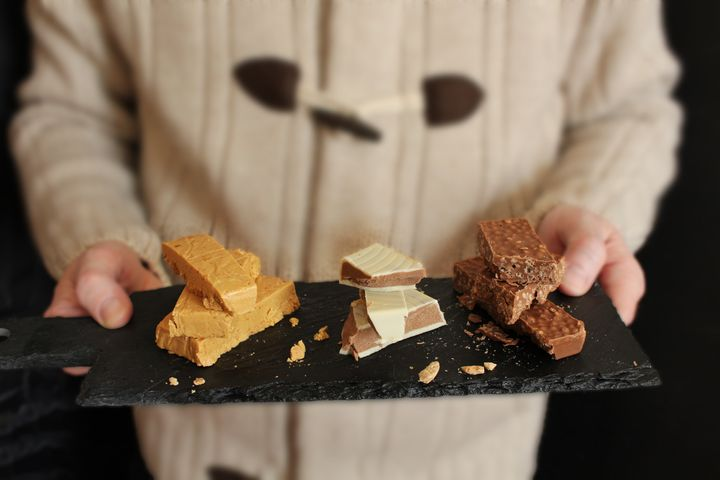 Man offering three types of Turron on slate