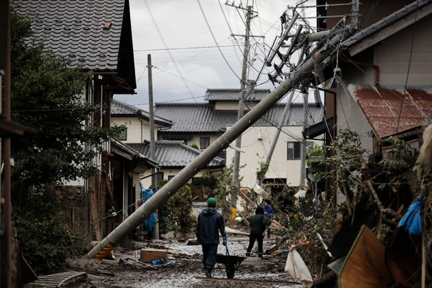 Residents walk along the mud-covered road in a neighborhood devastated by Typhoon Hagibis Tuesday, Oct....