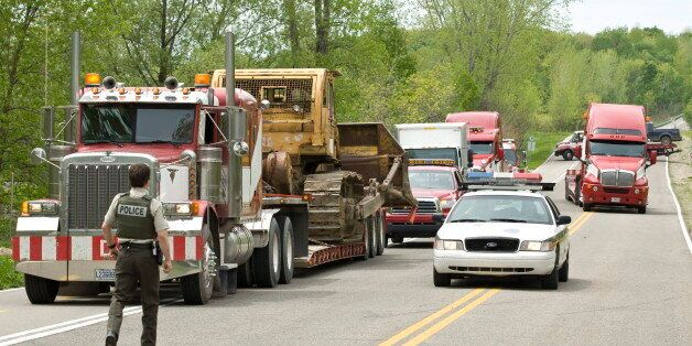 Police lead a convoy of seized heavy equipment following a police raid at the Kanesatake territory in Oka, Que., on May 19, 2009 in Montreal.