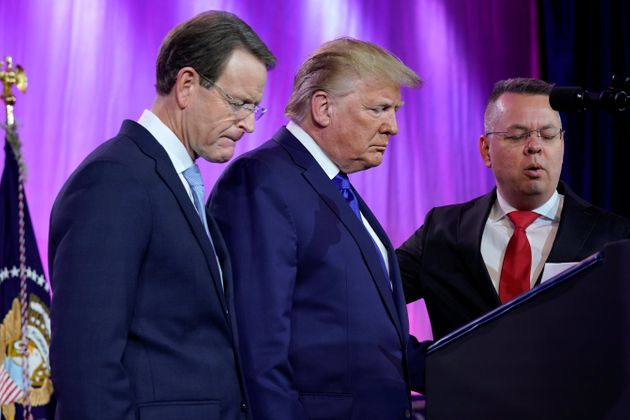 U.S. President Donald Trump prays between Tony Perkins, president of the Family Research Council, and...