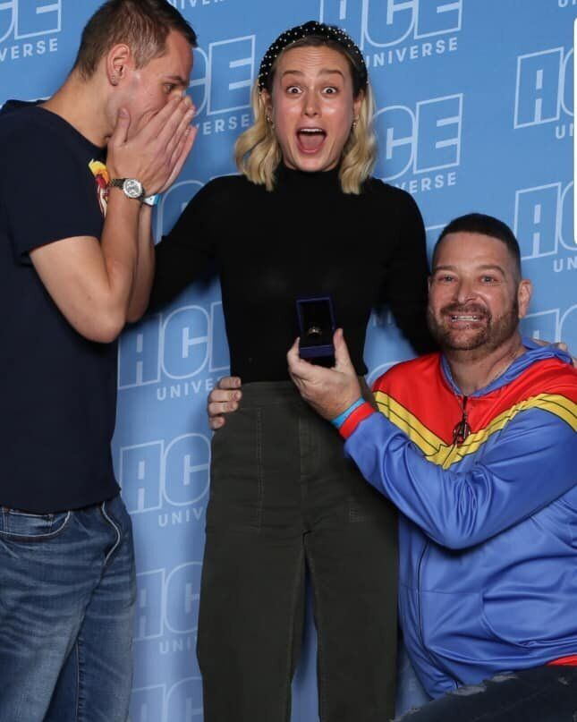 "Brie Larson (center) was caught off-guard this weekend when fan John Chambrone (right) used his Comic-Con meet-and-greet with the ""Captain Marvel"" star to propose to his boyfriend, Richard Owen."