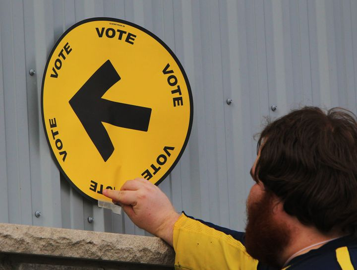 Elections Canada information officer Steven Moyer tapes a voting direction arrow sign to the fire hall in Kerwood, Ont., on Oct. 19, 2015.