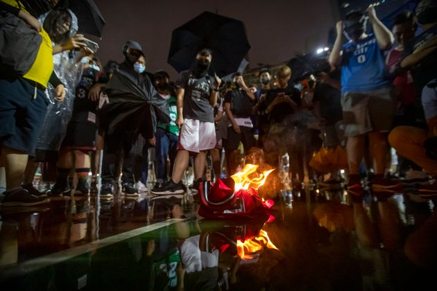 Demonstrators watch as a Lebron James jersey burns during a rally at the Southorn Playground in Hong...