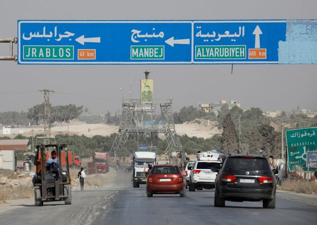 Cars pass under a road sign that shows the direction to Manbij city, at the entrance of Manbij, Syria...