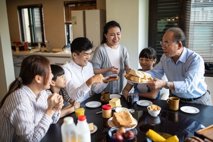 Three generation of Taiwanese family members having breakfast at home in the dining room, together