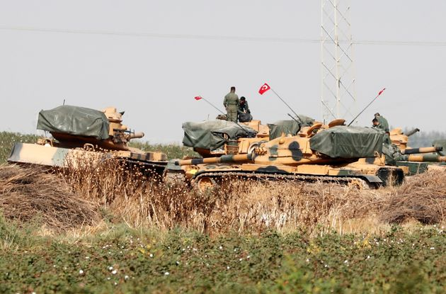 Turkish soldiers stand on top of tanks near the Turkish-Syrian border in Sanliurfa province, Turkey,...
