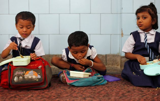 Schoolgirls eat their free mid-day meal, distributed by a government-run primary school, in New Delhi...