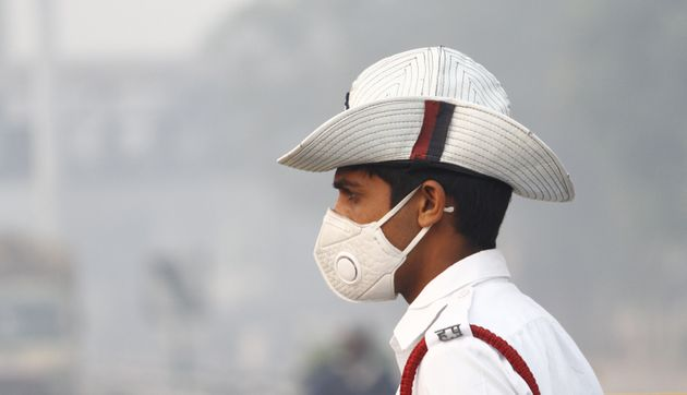 Traffic police personnel wear anti-air pollution masks amid heavy smog and air pollution, in November,...