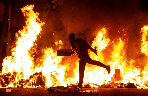 Un manifestante echa al fuego un cartón junto a la Delegación del Gobierno en
