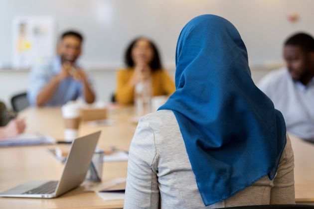 In this rear view, focus is on a Muslim businesswoman as she sits at a conference table with