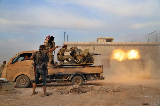 Turkey-backed Syrian opposition fighters fire a heavy machine-gun towards Kurdish fighters, in Syria's...