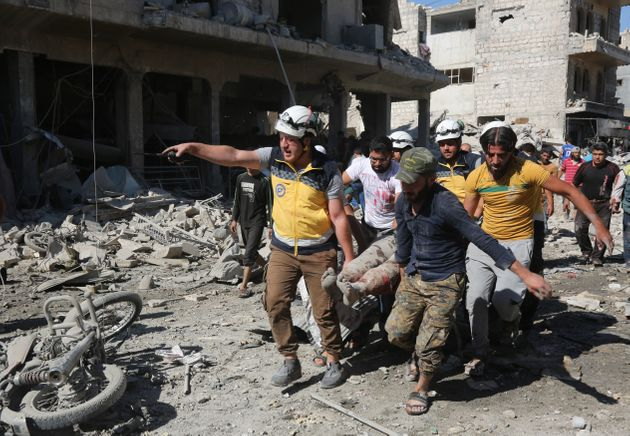 People carry wounded people to hospitals after Russian warplane carried out airstrikes on a marketplace...