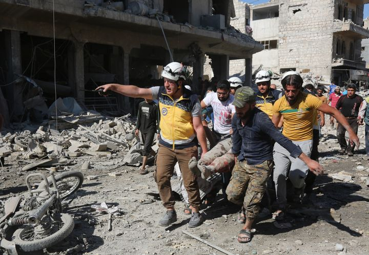 <strong>People carry wounded people to hospitals after Russian warplane carried out airstrikes on a marketplace in Maarat al-Numan district of Idlib, Syria on July 22.</strong>
