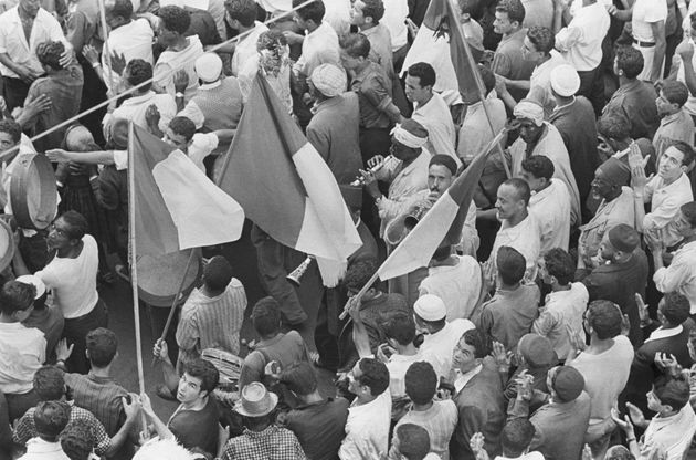 Overlooking Muslims waving the Algerian national flag and playing traditional music instruments while...