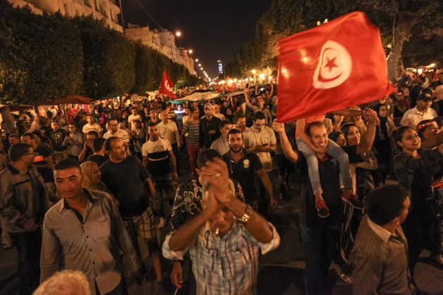 Supporters raise up flags of Tunisia and a giant flag of Palestine as they took part in the celebration...
