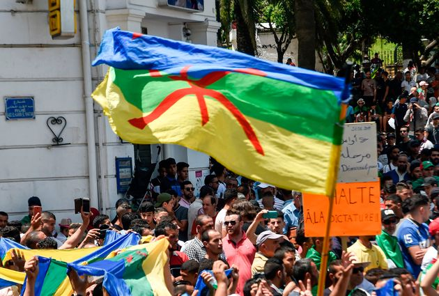 Algerian protesters wave Amazigh (Berber) flags as they chant slogans during the weekly Friday demonstration...