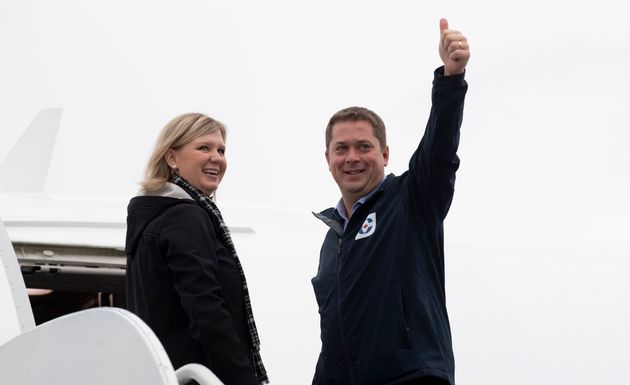 Conservative Leader Andrew Scheer gives the thumbs up beside his wife, Jill, as he boards his campaign...