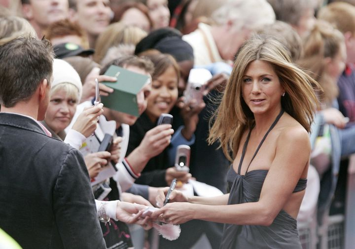 Jennifer Aniston greets fans as she arrives for the UK premiere of the film 'Break Up' in Leicester Square in London on June