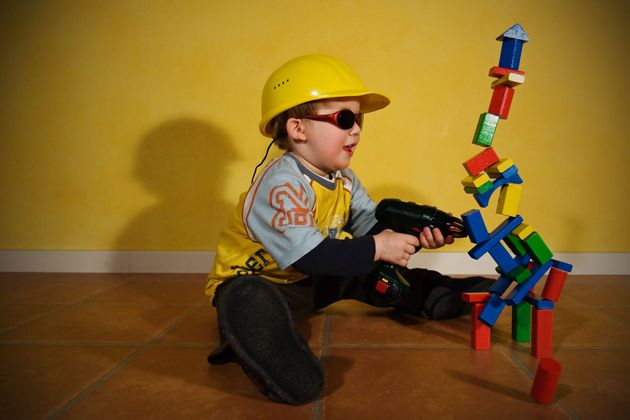 Stop motion shot of a toddler with a yellow helmet, sunglasses and an electric drill having fun in the...