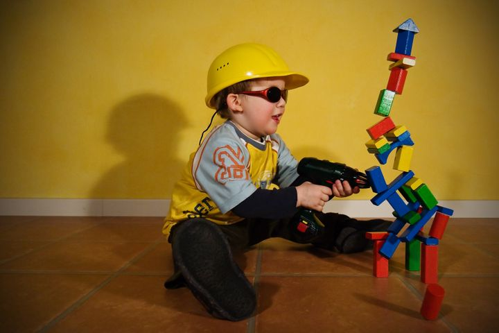 Stop motion shot of a toddler with a yellow helmet, sunglasses and an electric drill  having fun in the demolition of his creations made of building bricks.
