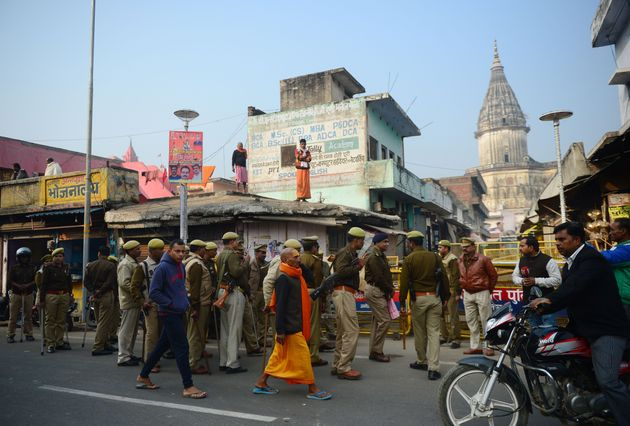 A sadhu walks past security personnel gathered on a street during the 26th anniversary of the demolition...