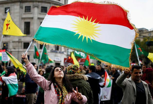 「クルドの旗」を掲げる女性。トルコのシリア侵攻に反対するイギリス・ロンドンのデモより