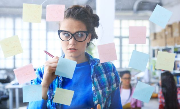 Young woman with eyeglasses writing on post-it notes on glass wall, in front of two female coworkers....