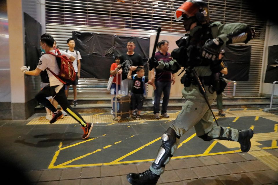 Police chase a protester in Hong Kong, Sunday, Oct.13, 2019. Protesters changed tactics and popped up...