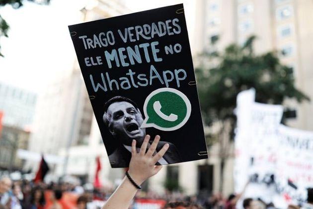 Una mujer sostiene una pancarta con la imagen de Jair Bolsonaro bajo un mensaje que dice