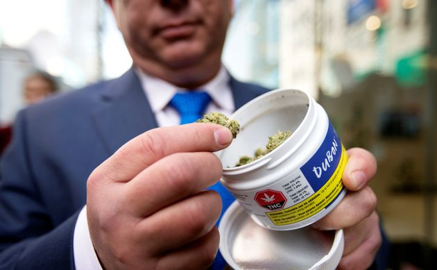A man shows off his cannabis purchase outside the Quebec Cannabis Society (SQDC) store, on the day Canada...