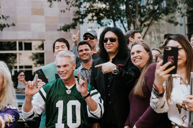"Intuit CEO Brad Smith flashes the ""rock on"" hand sign next to Kiss' Gene Simmons during Smith's 2018..."