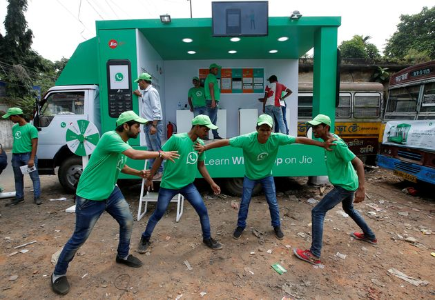 WhatsApp-Reliance Jio representatives perform in a street play during a drive by the two companies to...