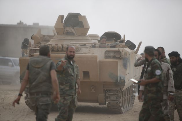 TAL ABYAD, SYRIA - OCTOBER 16: Syrian National Army members patrol an area with a tank in Tal Abyad,...