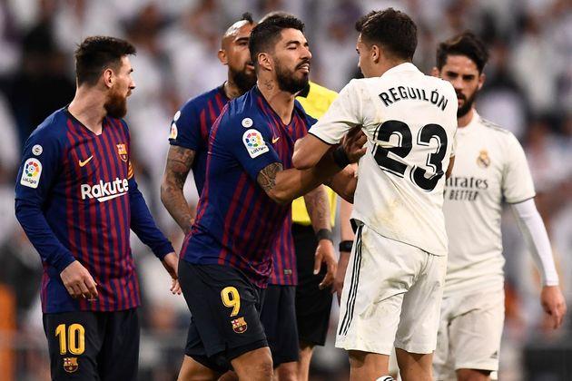 Barcelona's Uruguayan forward Luis Suarez (C) pushes Real Madrid's Spanish defender Sergio Reguilon during...