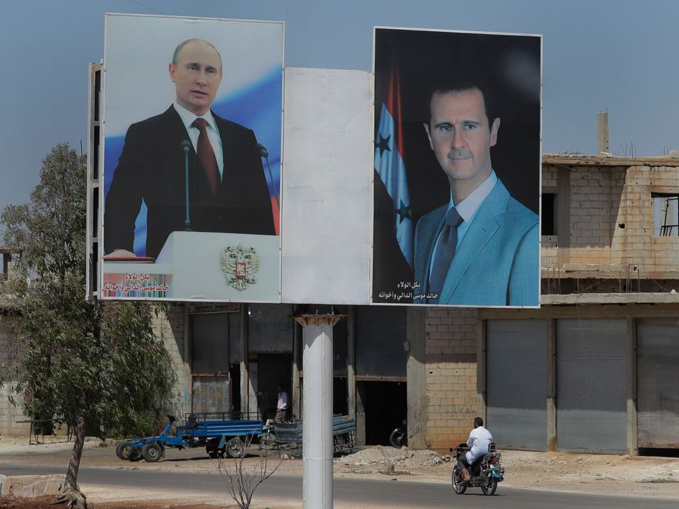 Πόστερ με τα πρόσωπα του Πούτιν και του Άσαντ στην πόλη Ρασταν της Συρίας.