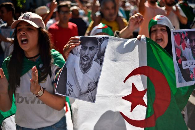 Algerian protesters chant while lifting national flags and pictures of a detained activist during an...