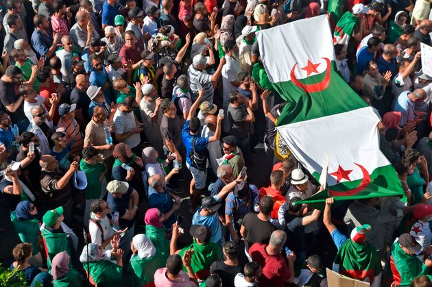 Algerian protesers chant slogans as some raise large national flags as they part in the 35th consecutive...