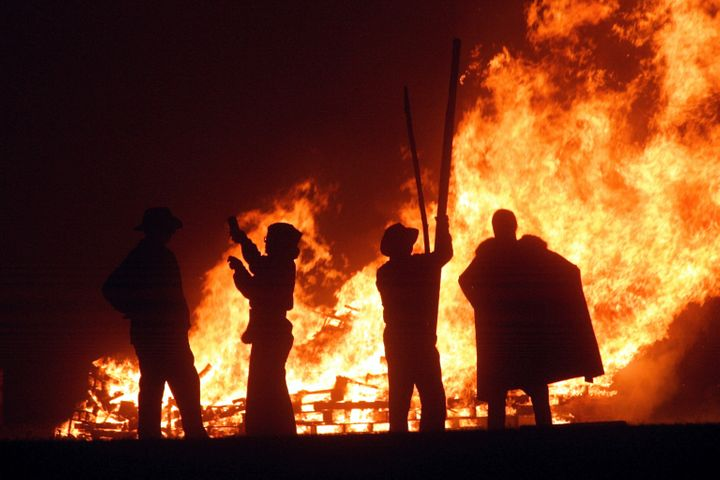 Revellers stand near the fires during the first of the Bonfire Night celebrations on Sept. 25, 2004 in Burgess Hill, England. Bonfire Night is related to the ancient festival of Samhain, the Celtic New Year otherwise known as Halloween.
